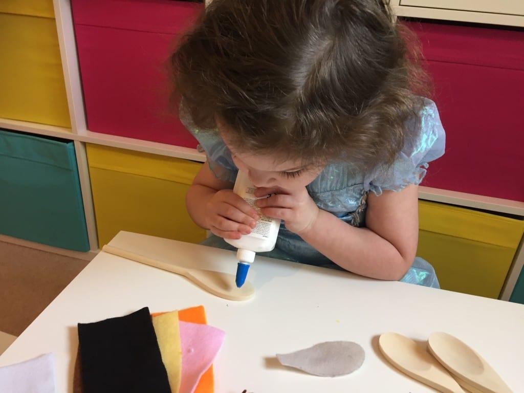 Isla glueing the felt onto her wooden spoon