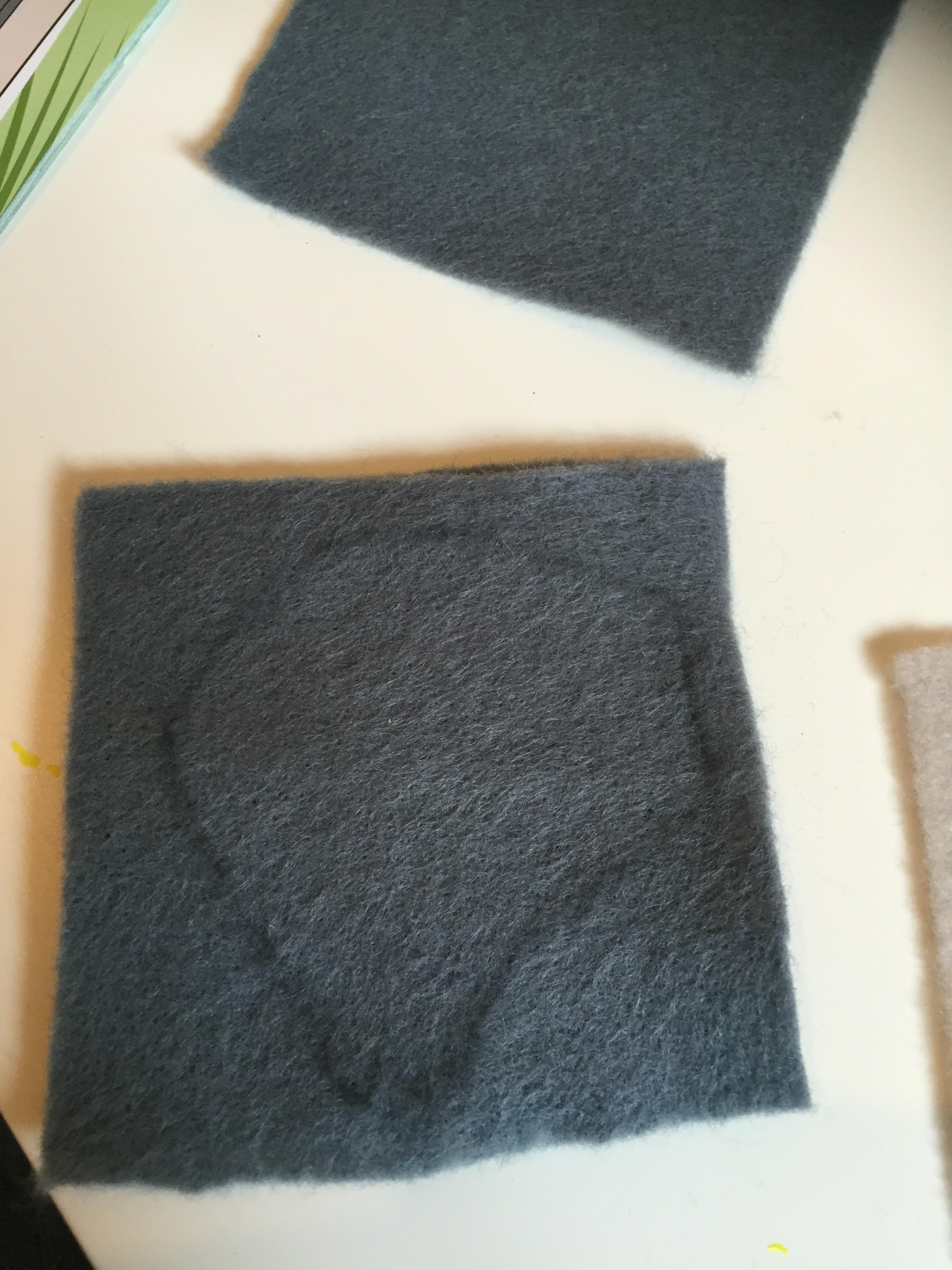 drawing an ear shape onto dark grey felt