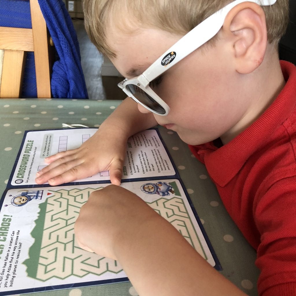 Oliver using the activity book from his Mecury pack.