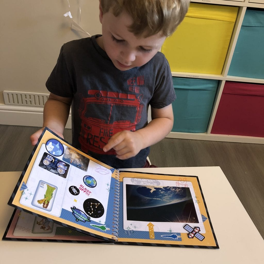 Oliver looking in his space journey mission log book