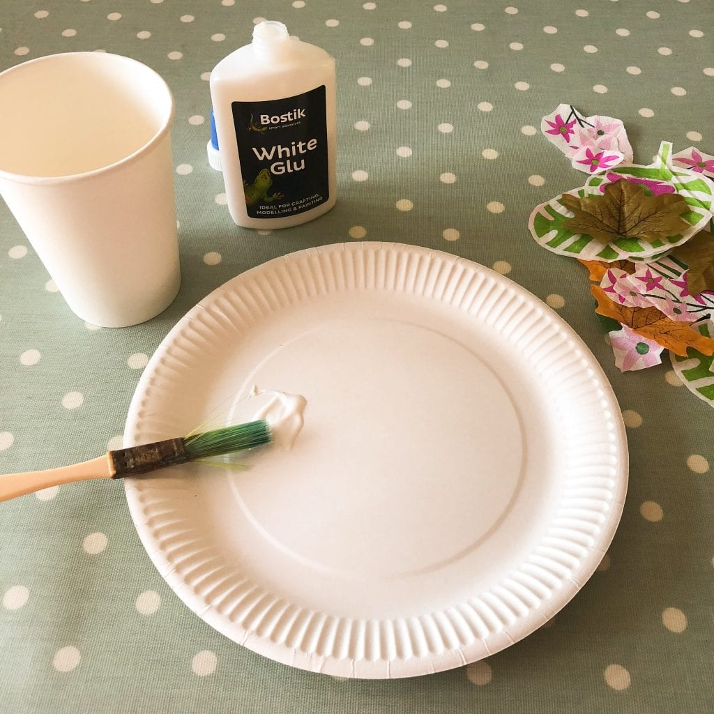 painting glue onto the paper plate