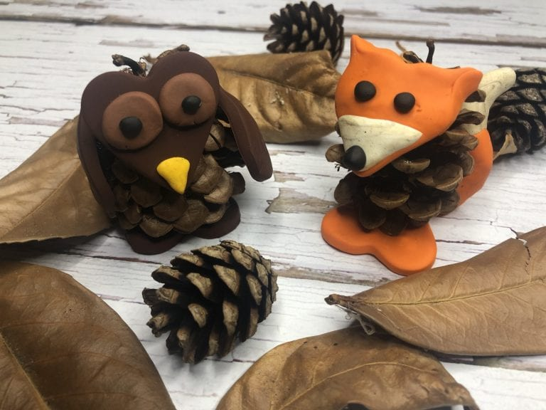 A pine cone and polymer clay fox and owl sitting amongst some autumnal leaves and pinecones
