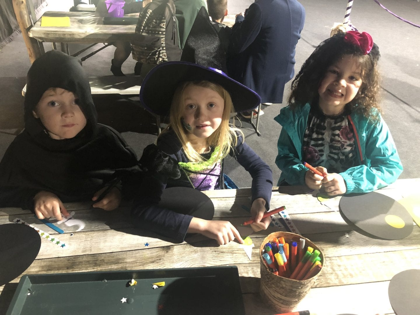 3 children sitting at a table doing some Halloween crafts
