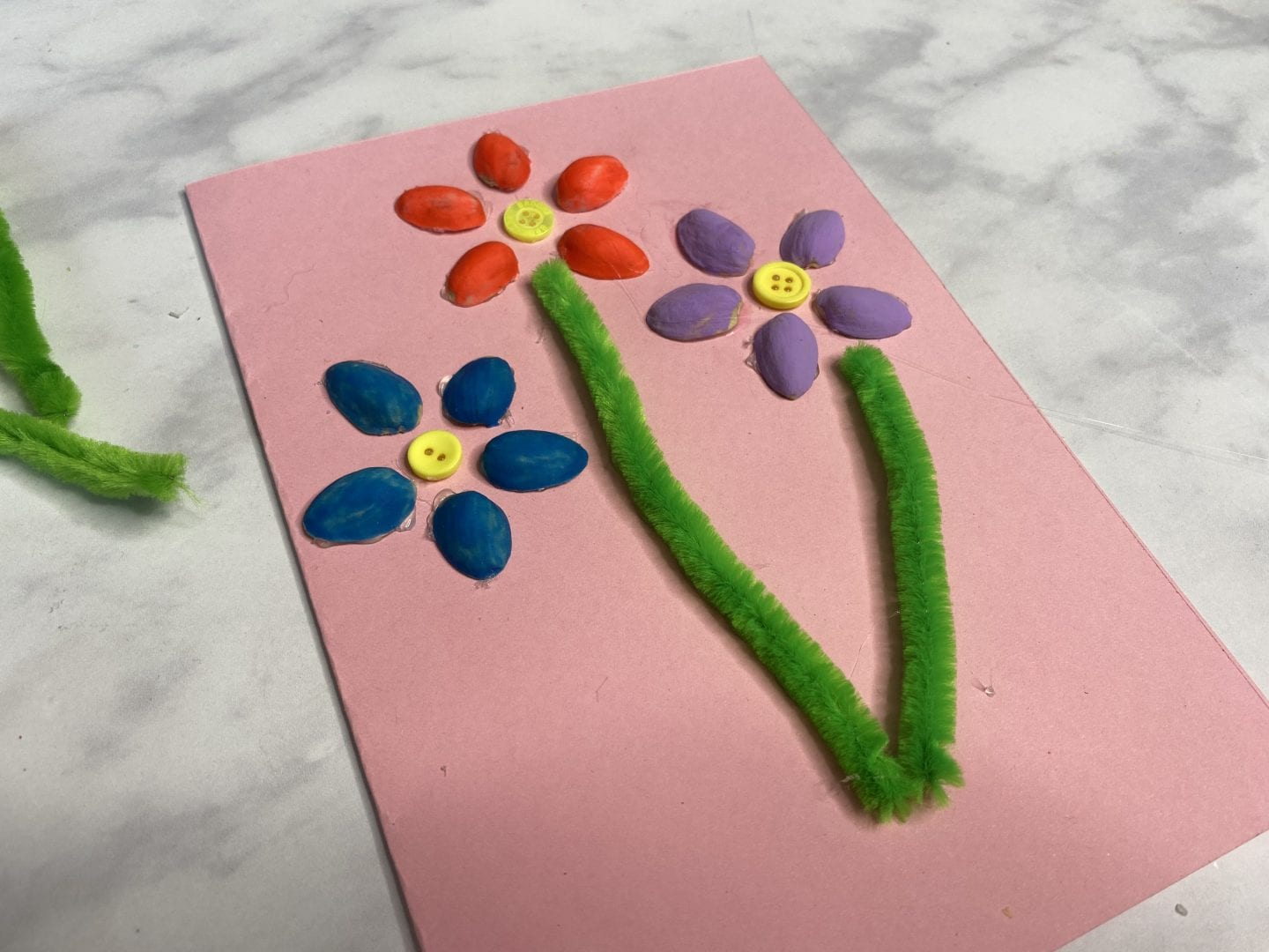 half finsihed card. sticking on pipe cleaners for the flower stems.