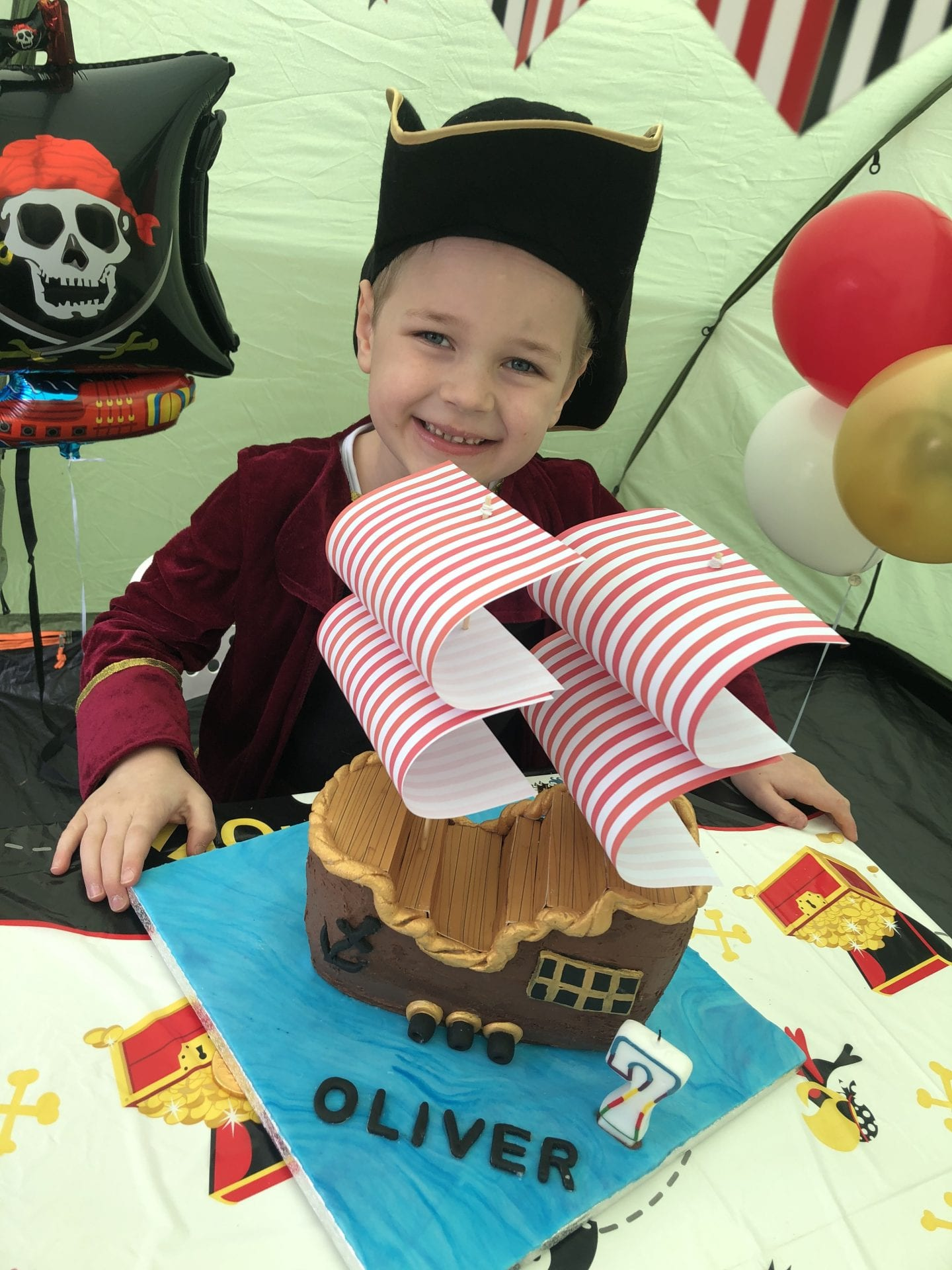 Oliver sat behind his pirate ship birthday cake