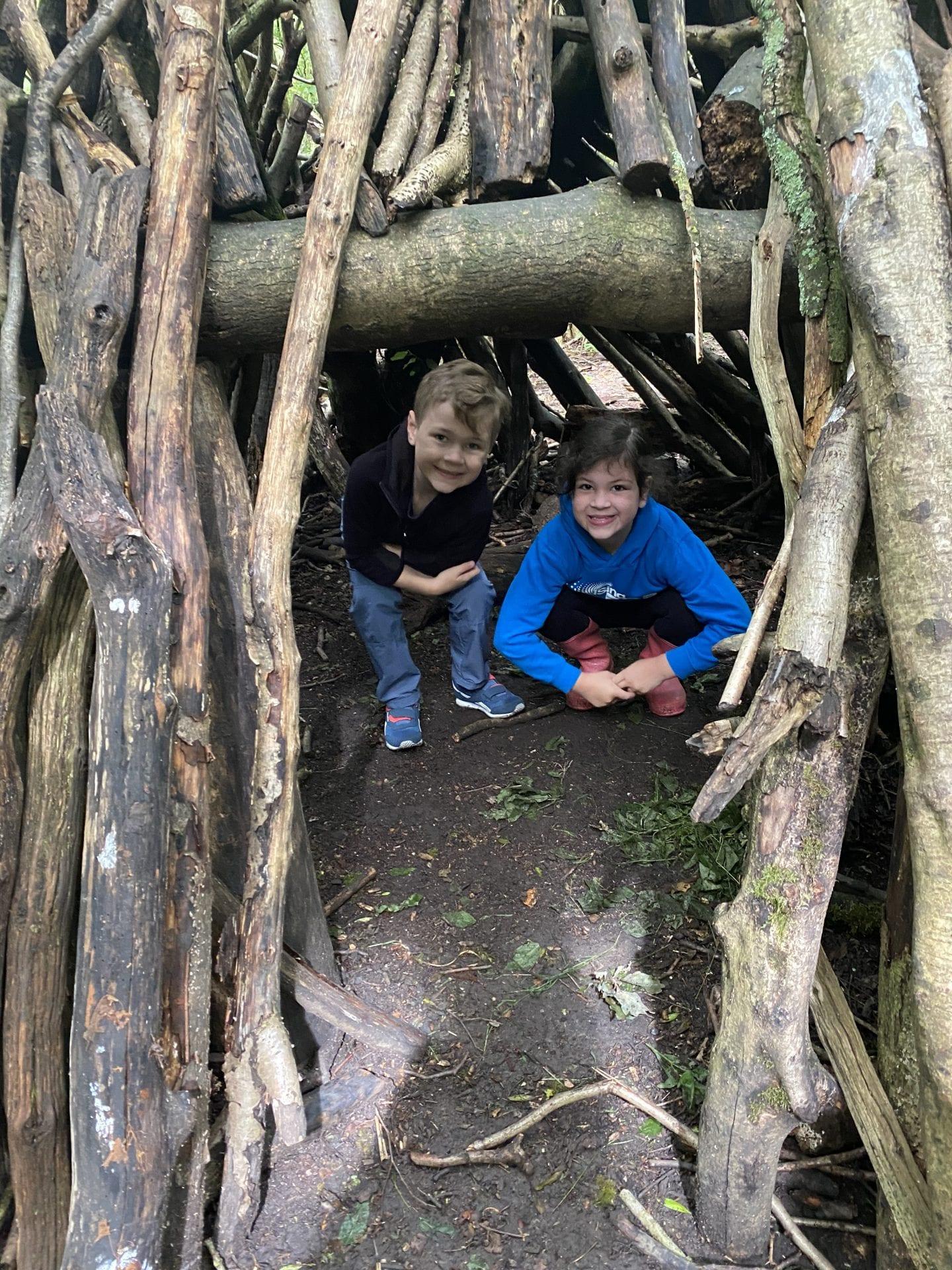 2 children in a den built from logs