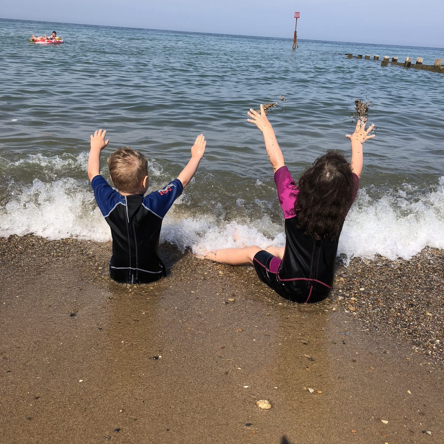 2 young children sitting on a beach in the surf