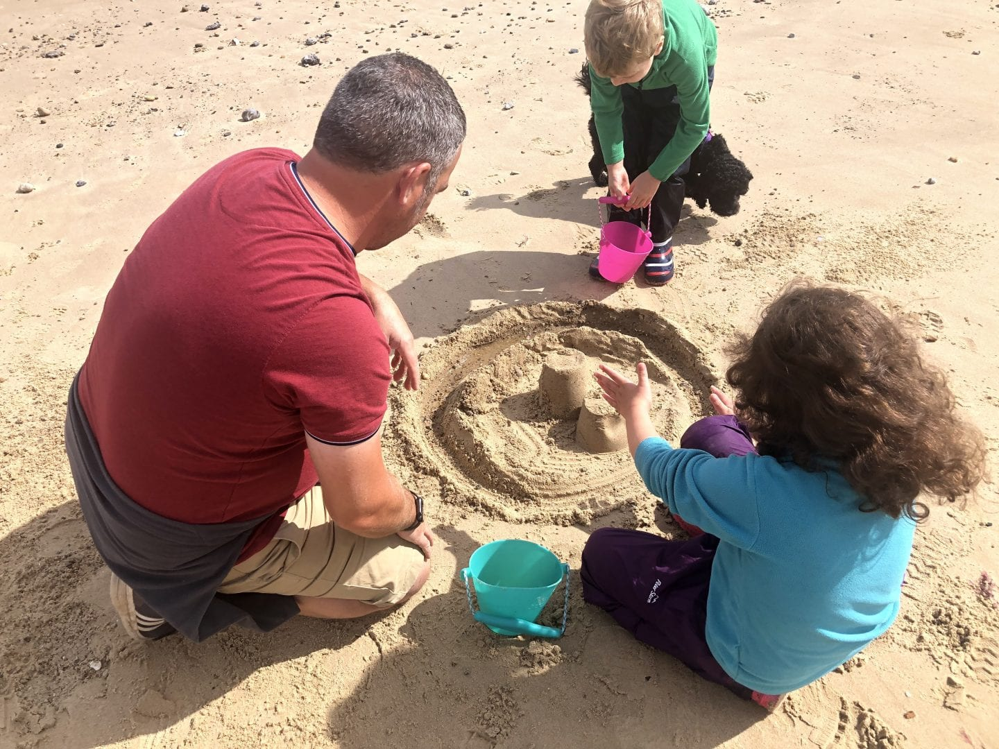 young family building sandcastles