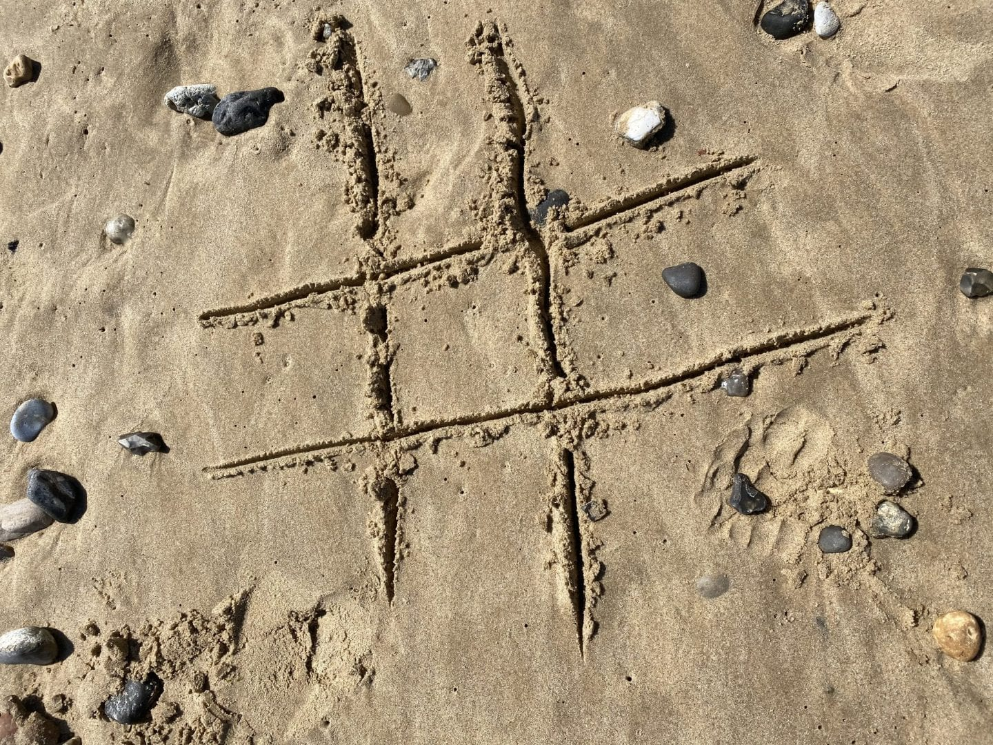 tic tac toe drawn in the sand