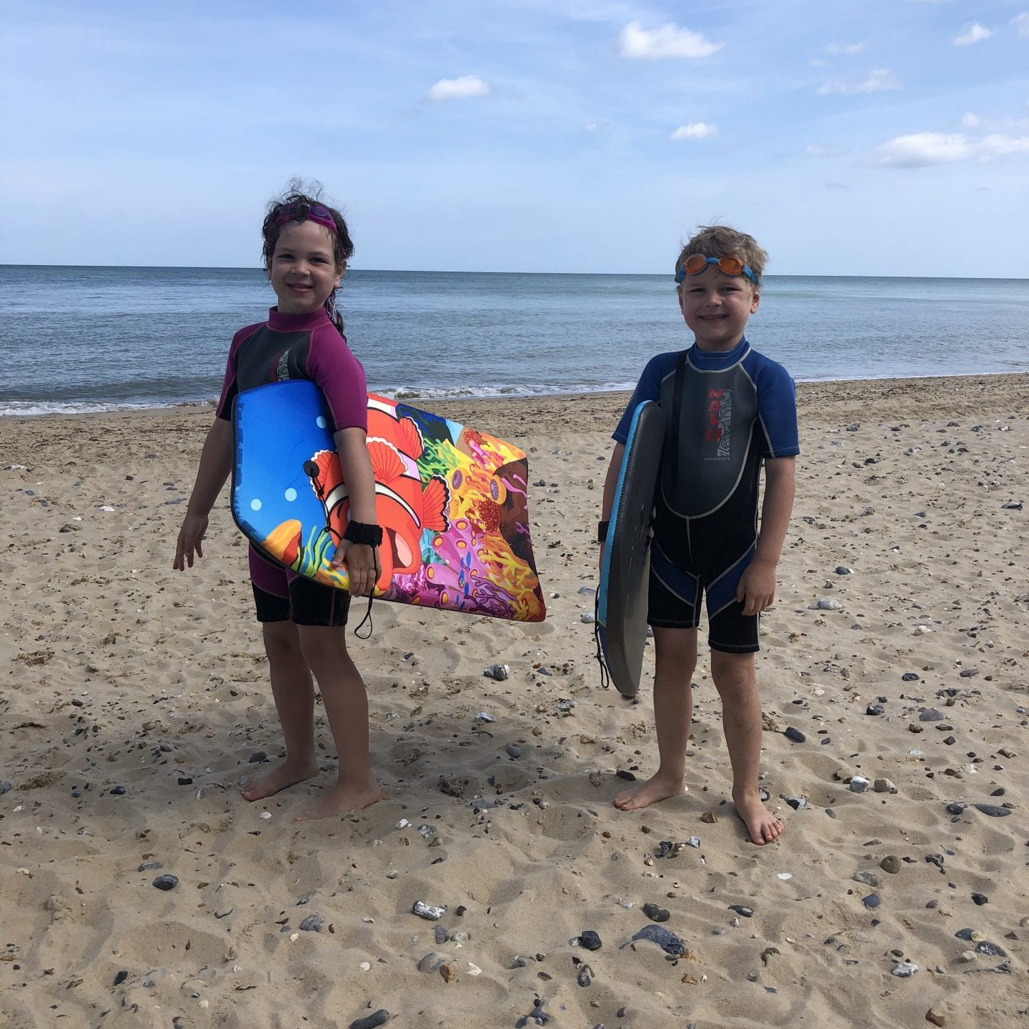 2 children holding body boards on a beach