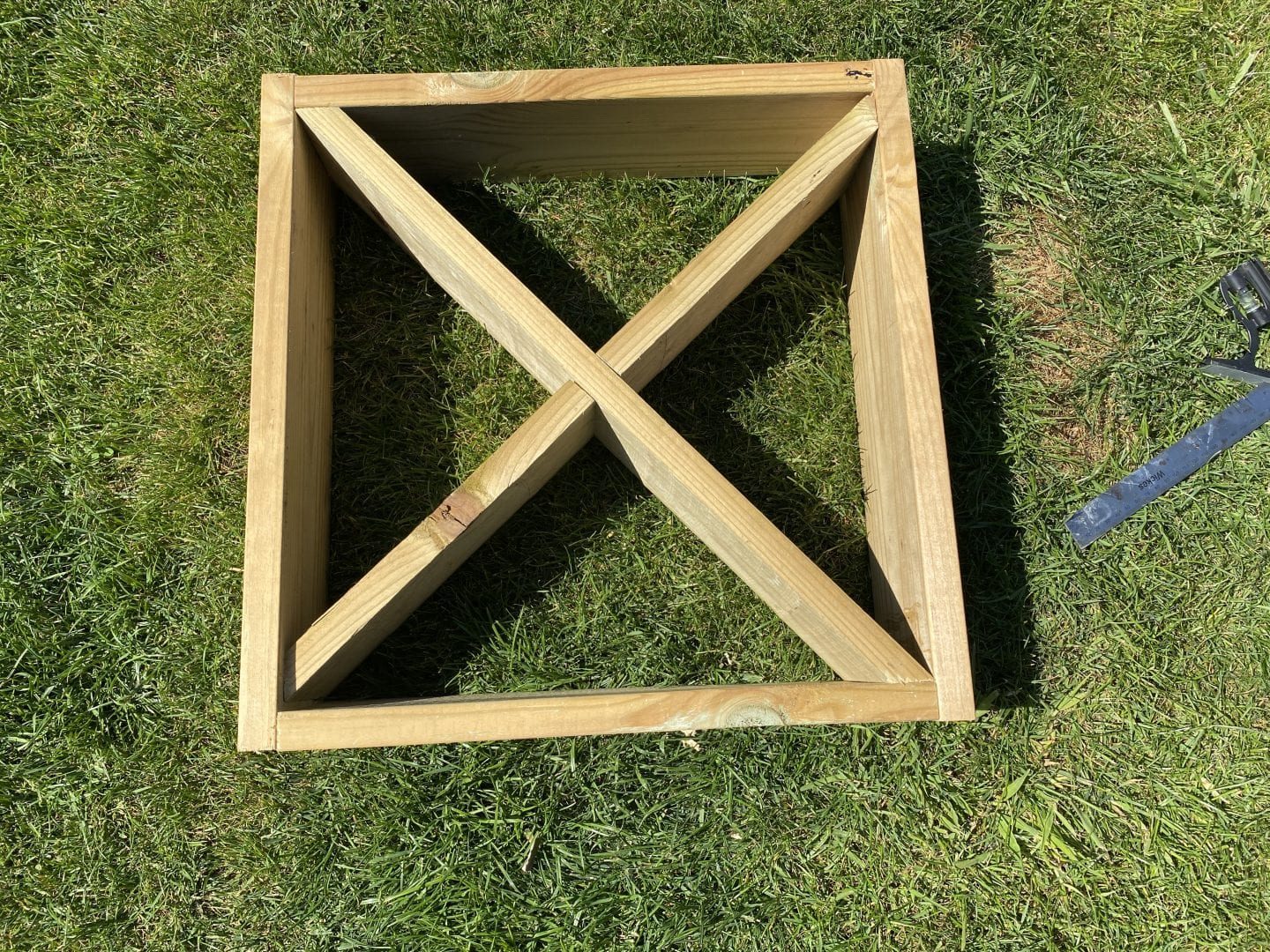 square wooden frame, with two diagonal pieces of timber to divide it into 4 sections