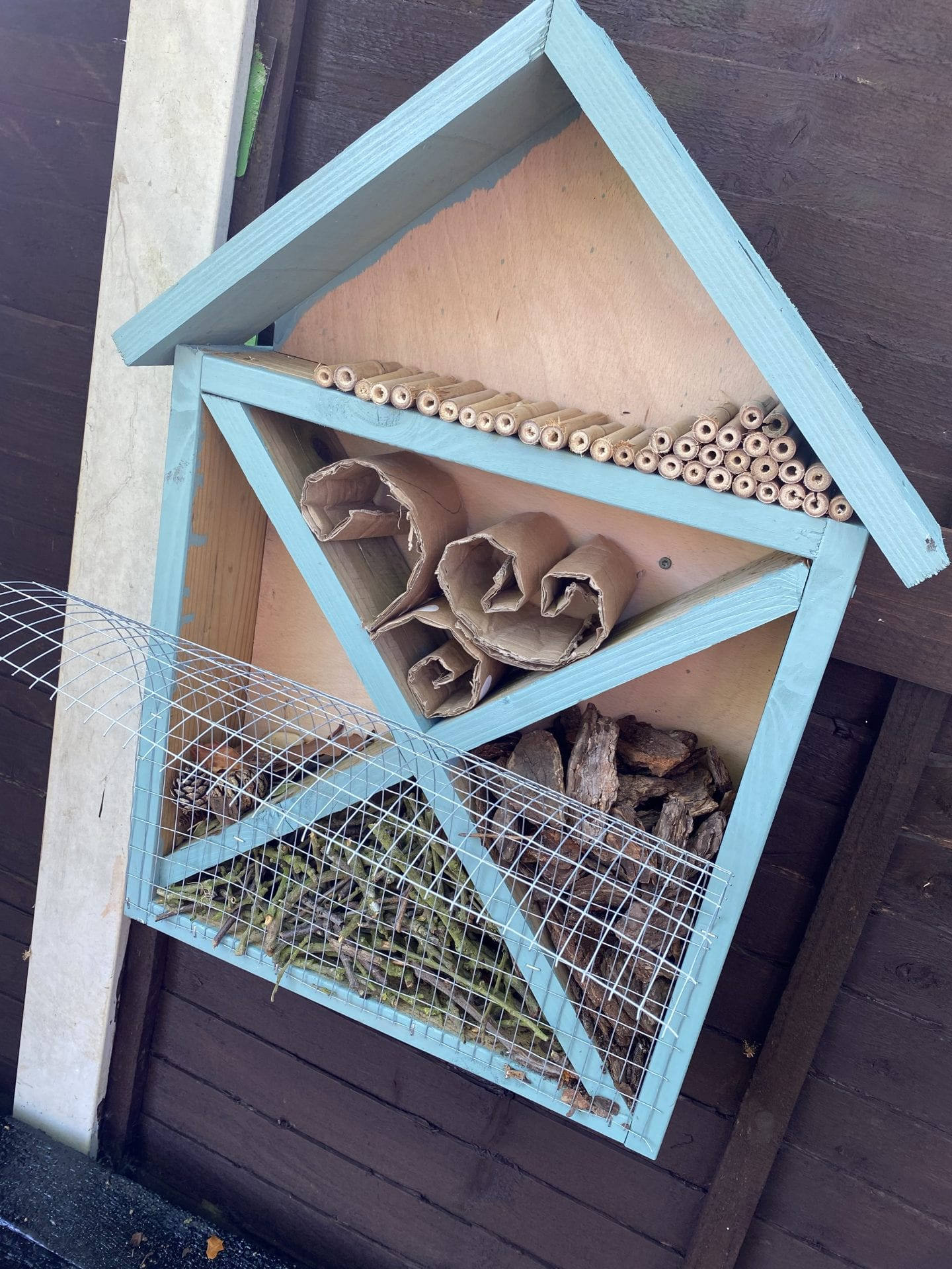 Filling up the bug hotel with hollow tubes, bark, sticks, cardboard and dry leaves and pine cones.