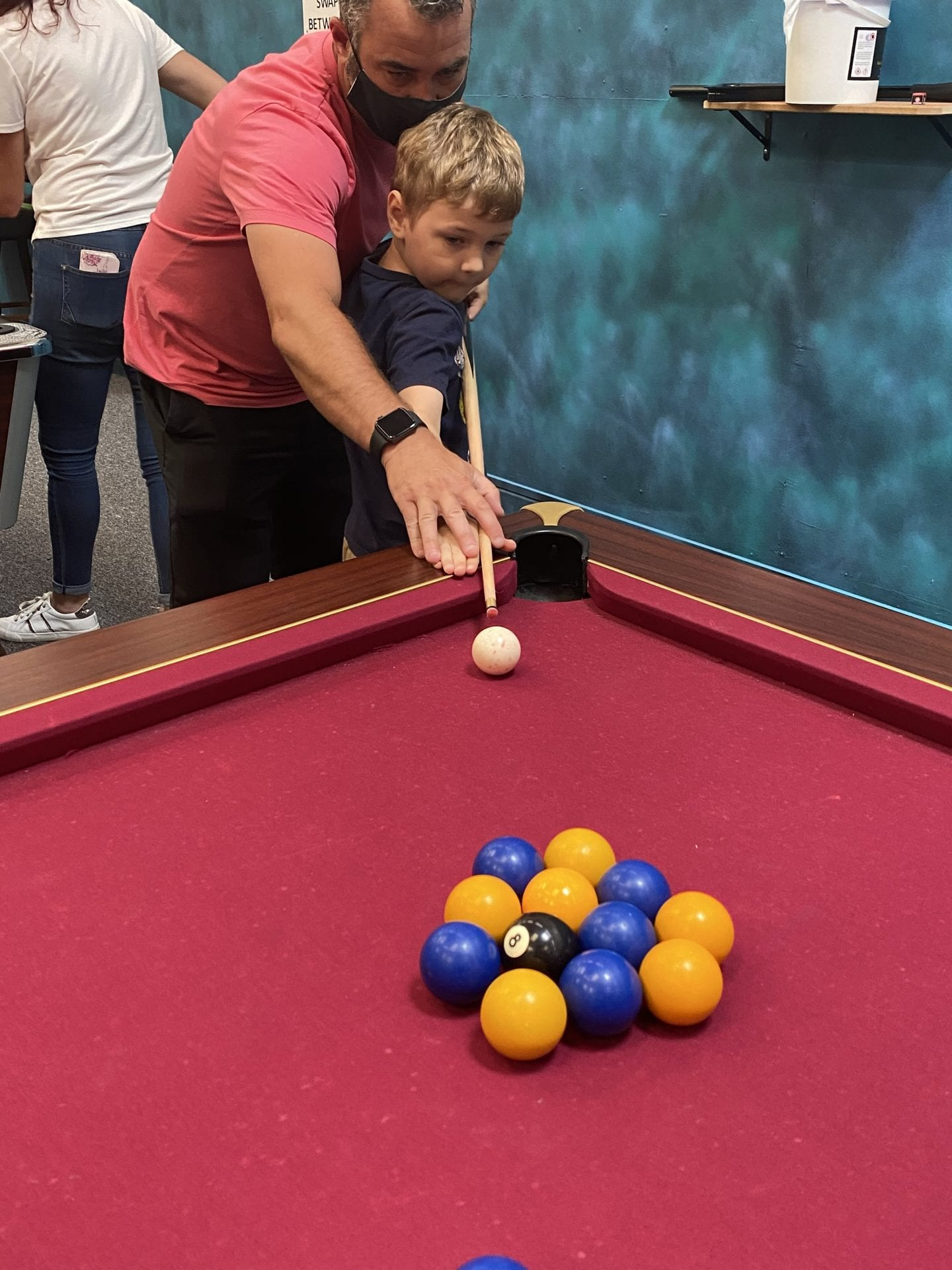 A dad teaching his son how to hit the que ball in pool