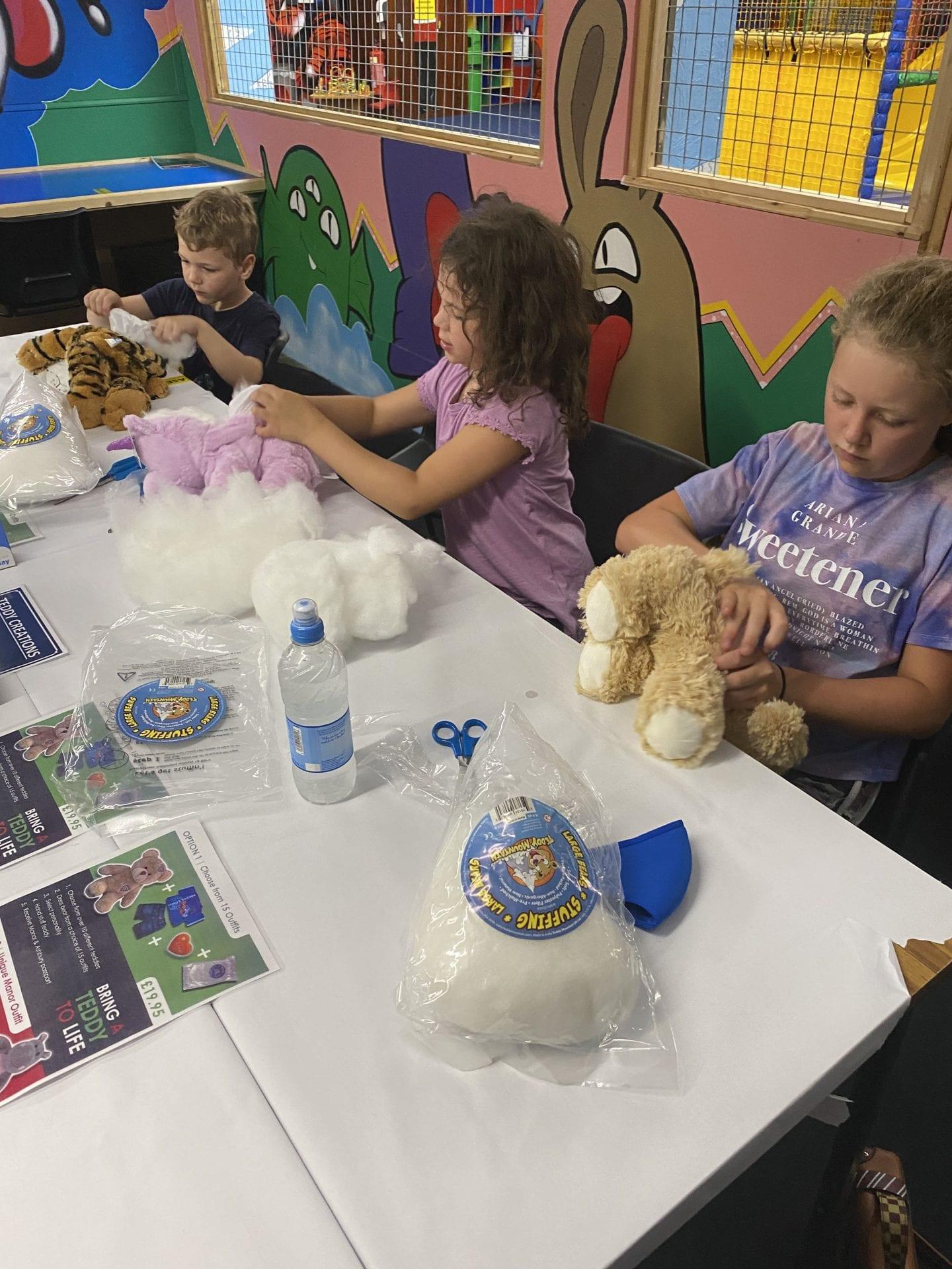 3 children making teddy bears