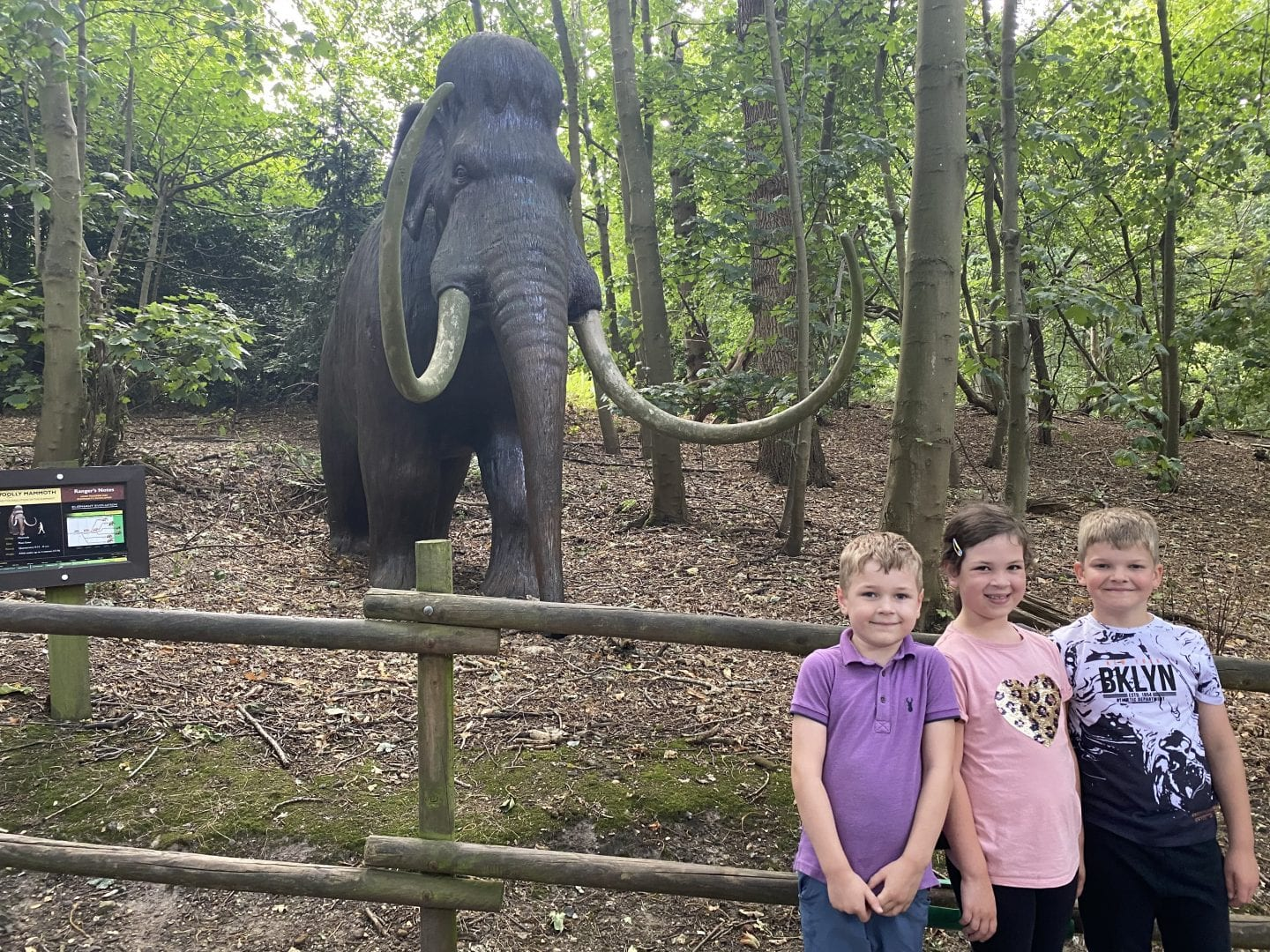 3 children standing in front of a staue of a wooly mammoth