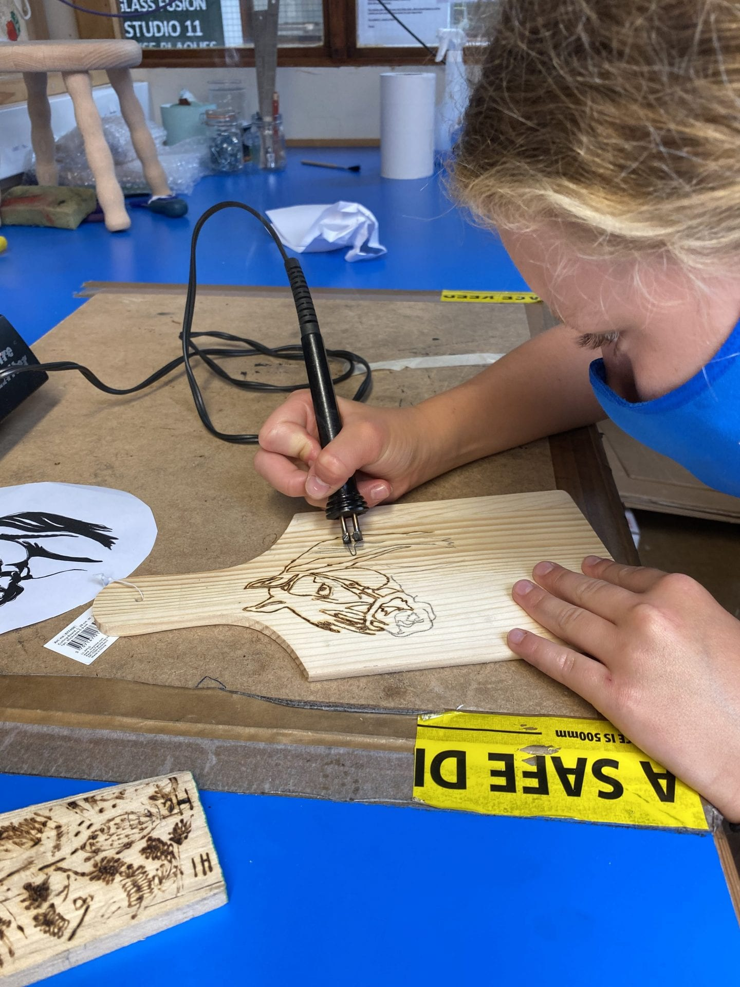 A young girl using pyrography to draw a horse on a small wooden chopping board