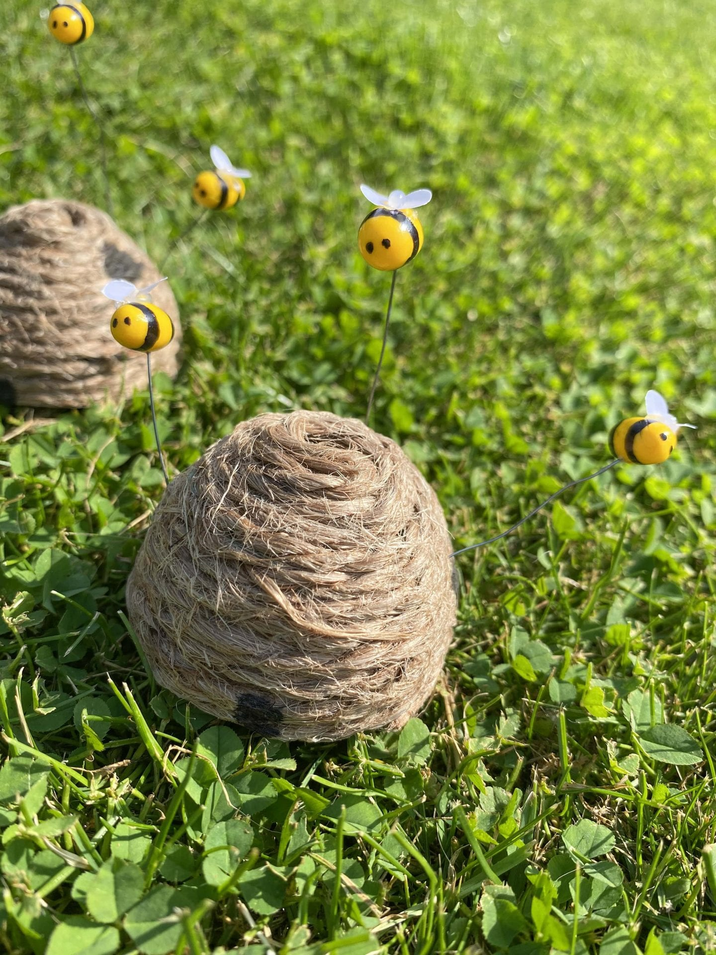 A finished bee skep with polymer bees on some grass
