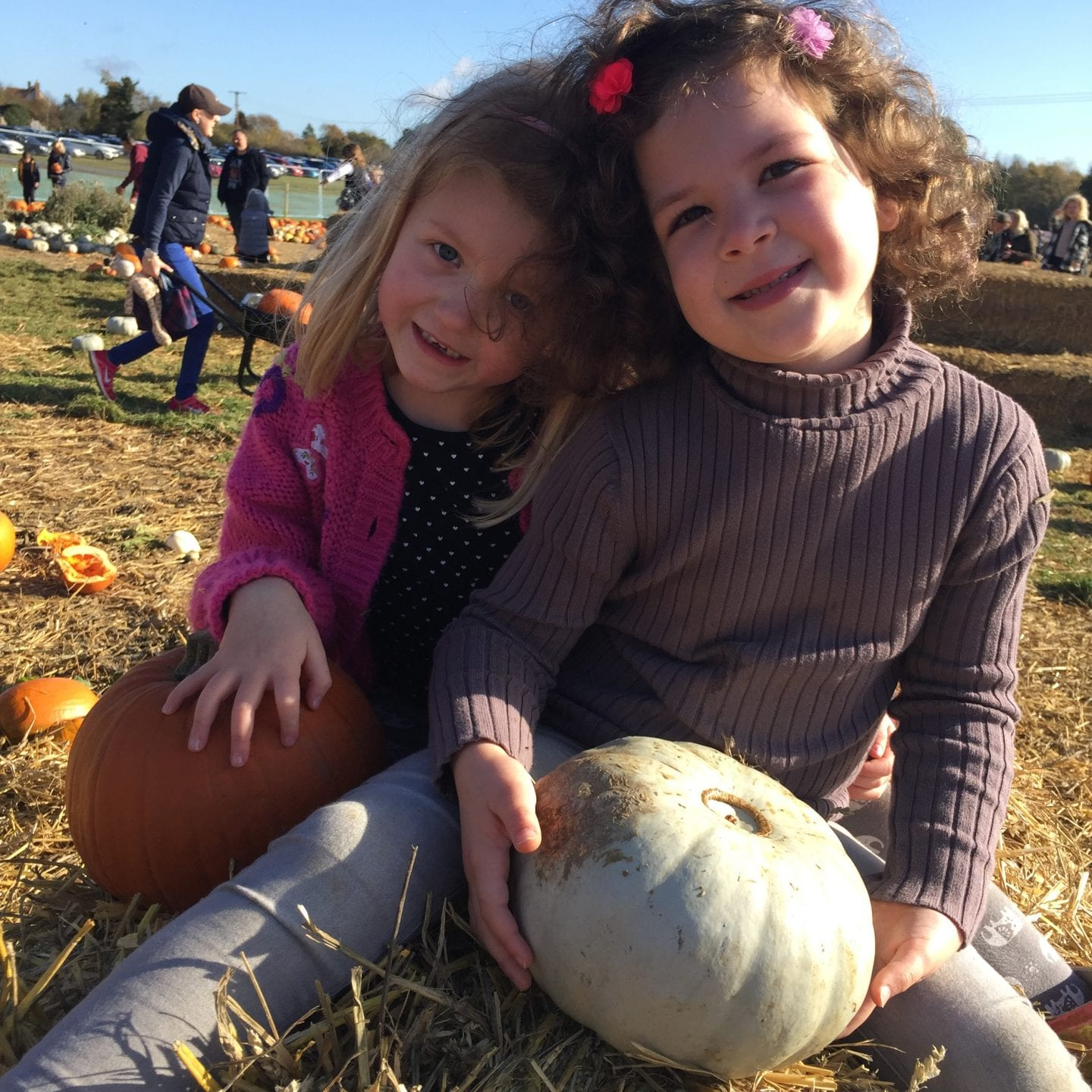 2 young girls sitting on a straw bale with their pumpkins