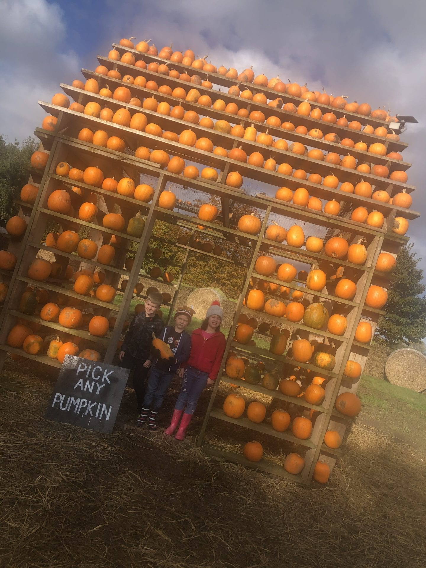 3 children standing in the entance of the 'Pumpkin House'